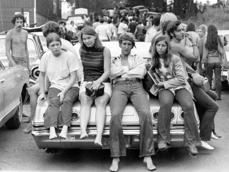 Barn som sitter på en bil under Woodstock-festivalen (foto: Ric Mannining, CC:by-nc-sa)