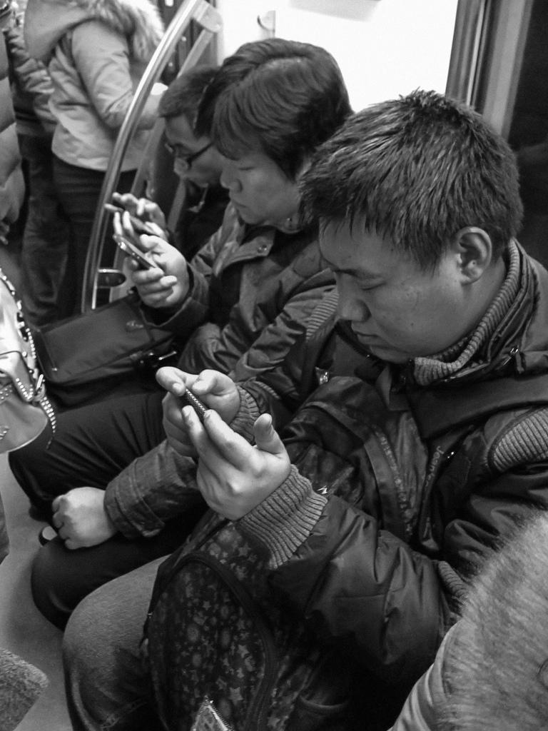 Et vanlig syn på t-banen i Beijing: Full konsentrasjon om smarttelefonen. (Foto: Lu Feng. CC: by-nc-nd)