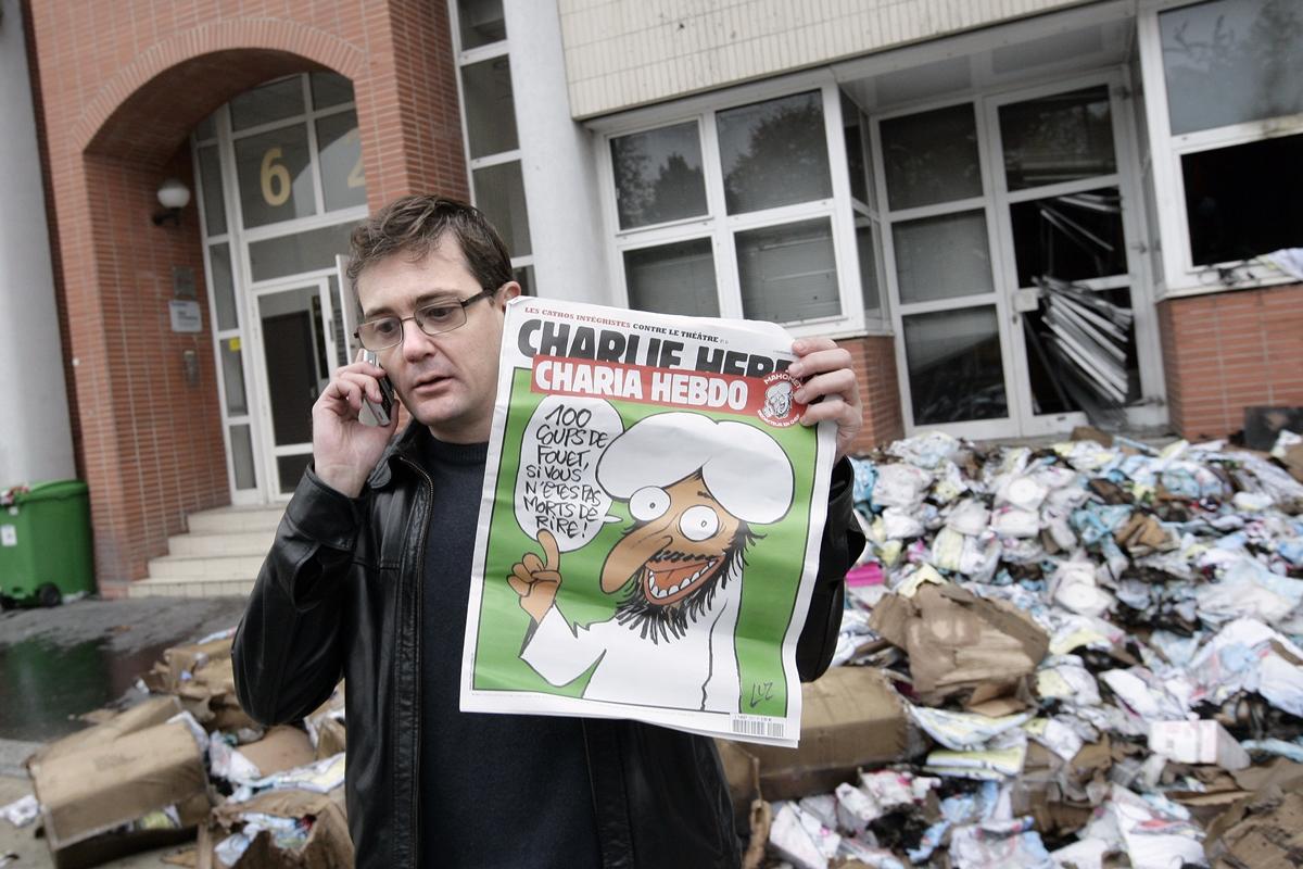 """Paris 2. november 2011: Sjefredaktør i Charlie Hebdo Stéphane Charbonnier (Charb) holder en utgave av bladet med Muhammed-karikatur på forsiden. Tekst i snakkeboblen: """"100 piskeslag om du ikke dør av latter"""". Redaksjonslokalene i bakgrunnen ble ødelagt av en brannbombe natten før. (Foto: Alexander Klein, AFP/NTB Scanpix)."""
